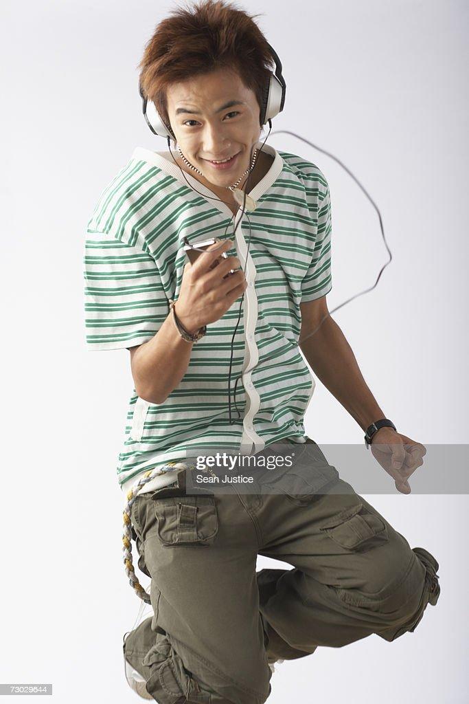 Teenage boy listening to mp3 player : Stock Photo