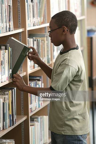 Teenage boy looking at books in library