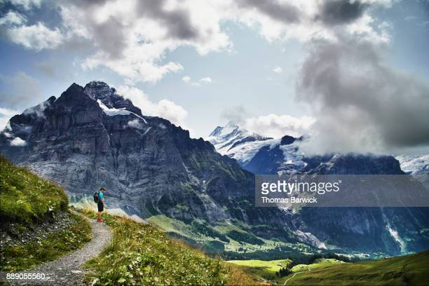 Teenage boy looking at view of Grindelwald valley in Swiss Alps while hiking