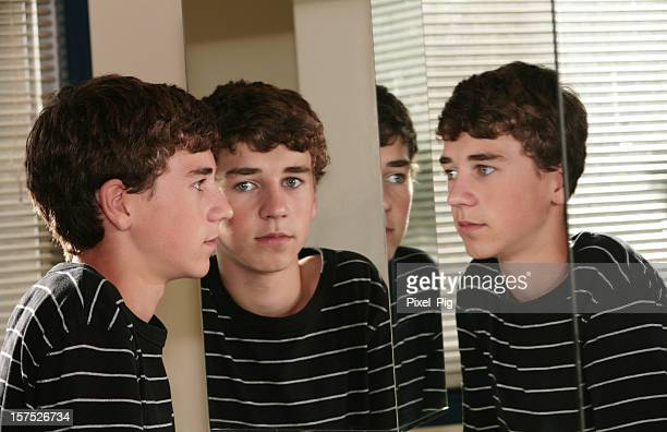 Teenage boy looks at his multiple reflections