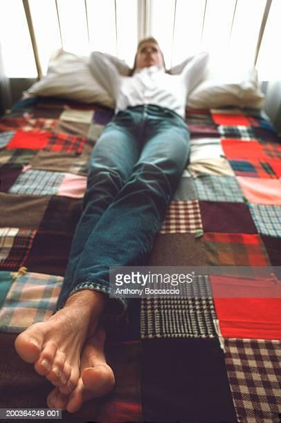 Teenage boy (16-18) lying on bed