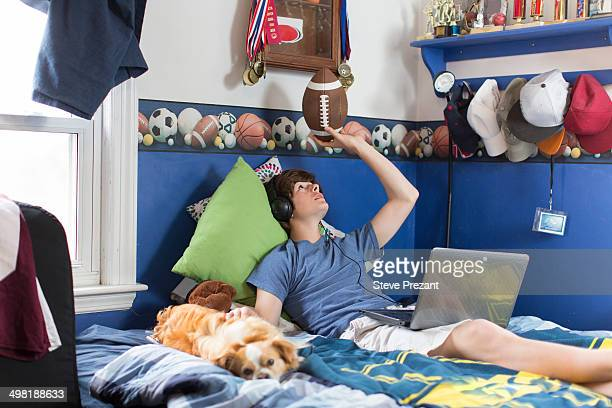 Teenage boy lying on bed with laptop computer, football and dog