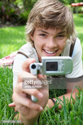 Teenage boy (16-18) lying on grass, using camera phone, portrait : Stock Photo
