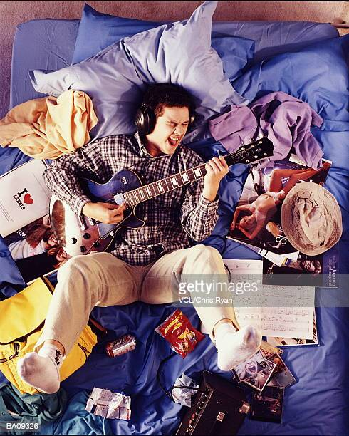 Teenage boy(15-17) lying on untidy bed, playing guitar overhead view.