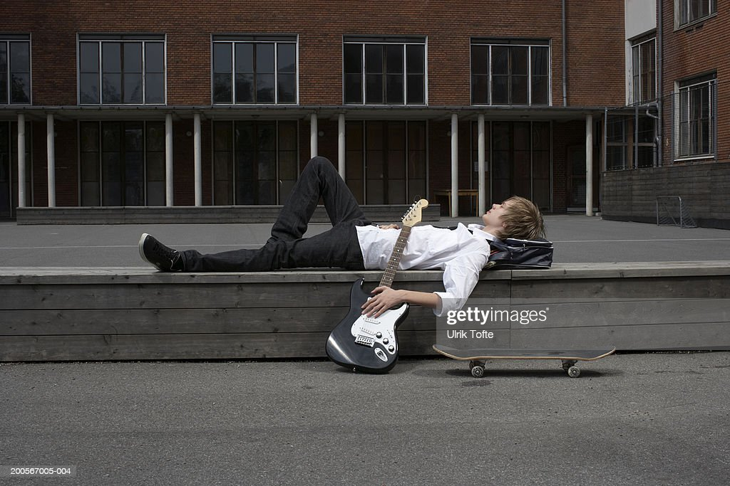 Teenage boy (14-15) lying on wall in front of school with electric guitar and skateboard, side view : Stock Photo