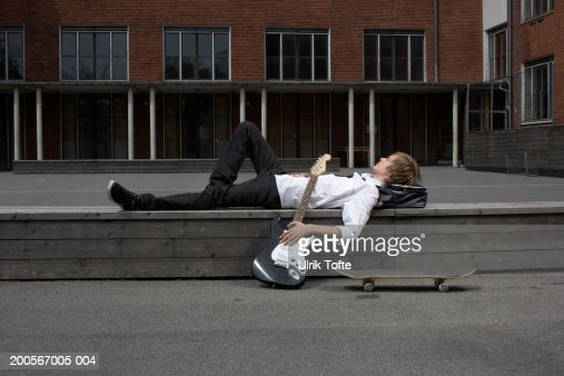 Teenage boy (14-15) lying on wall in front of school with electric guitar and skateboard, side view : Photo