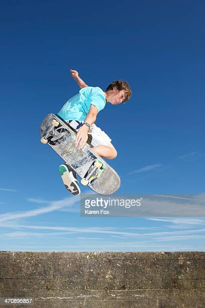 Teenage boy mid air on skateboard