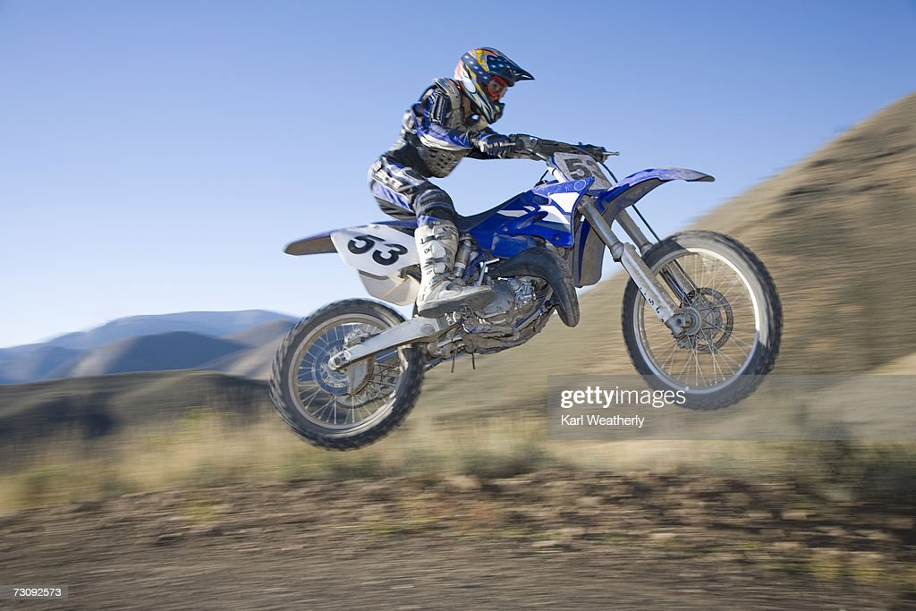 Teenage boy (13-15) motorbiking down dirt road : Stock Photo