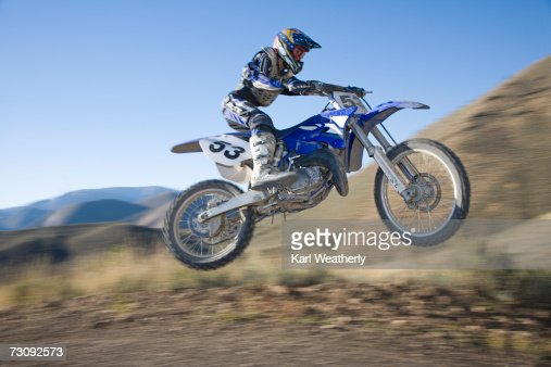 Teenage boy (13-15) motorbiking down dirt road : Foto de stock