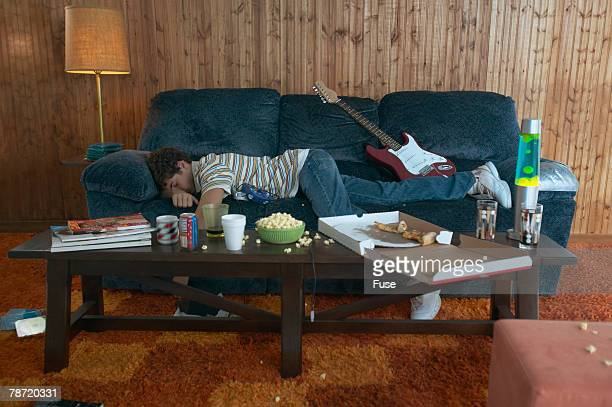 Teenage Boy Napping in Messy Living Room