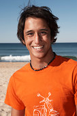 Teenage boy (16-18) on beach, smiling, portrait, close-up
