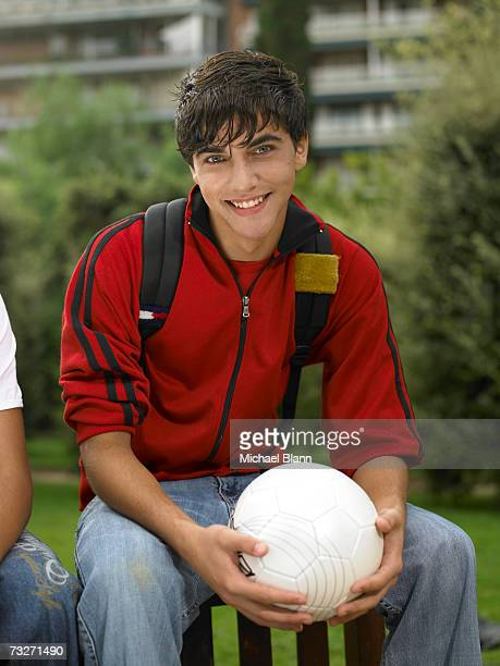 Teenage boy (15-17) on bench, holding soccer ball at park