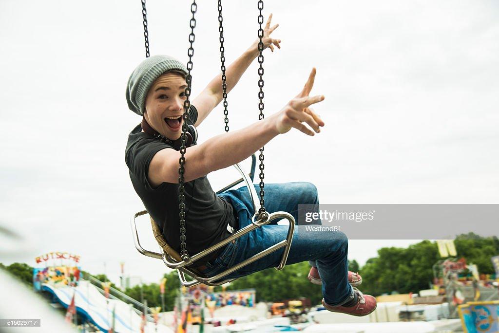 Teenage boy on chairoplane at fun fair