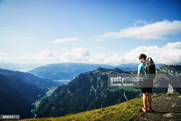 Teenage boy on hike in Swiss Alp taking in view from Mannlichen of Interlaken Switzerland