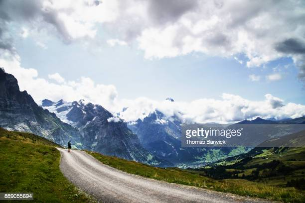 Teenage boy on hike in Swiss Alps taking picture with smartphone of Grindelwald valley