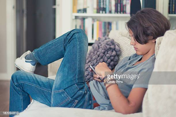 Teenage boy on the couch texting on his cell phone