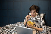 Portrait of teenage boy using laptop in bed and eating chips while watching movies at home, copy space