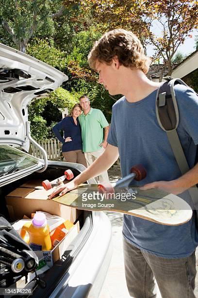 Teenage boy packing skateboard into car
