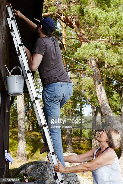 Teenage boy painting house while woman holding ladder, Sweden