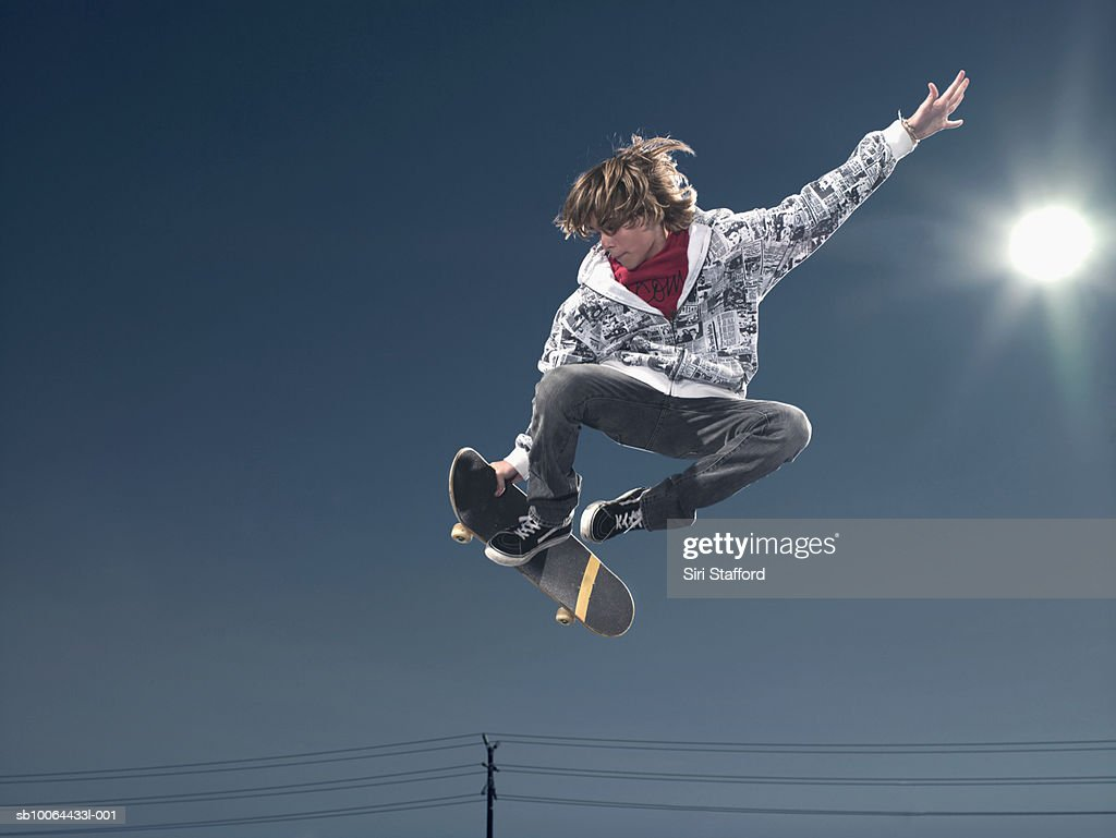 Teenage boy (16-17) performing jump on skateboard, low angle view : Stock Photo