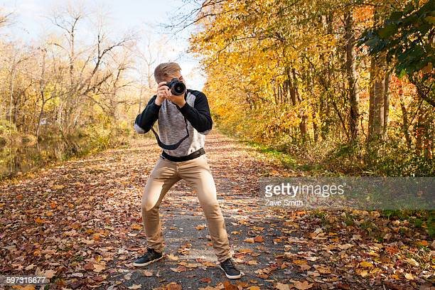 Teenage boy photographing from road autumn park forest