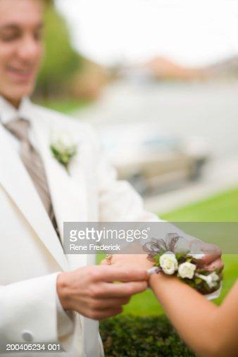 Teenage boy (14-16) placing wrist corsage on teenage girl (14-16) : Stock Photo