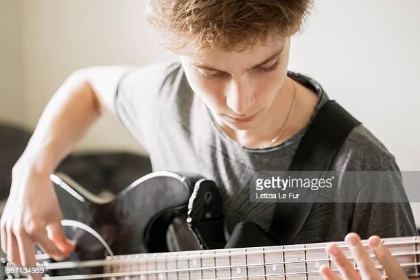 Teenage boy playing a guitar