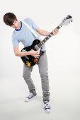 A teenage boy playing a guitar