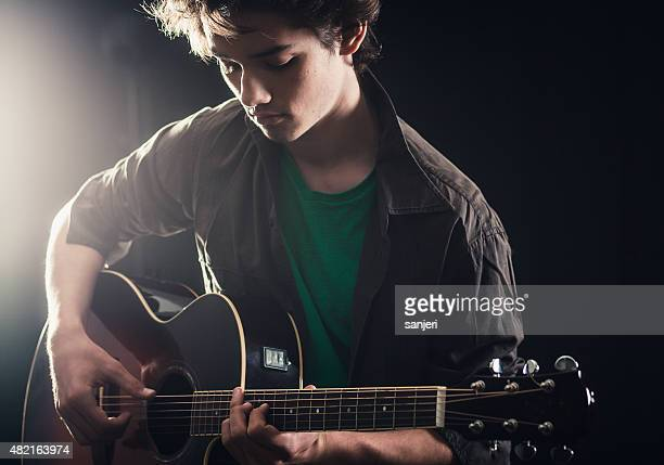 Teenage boy playing acoustic guitar on stage