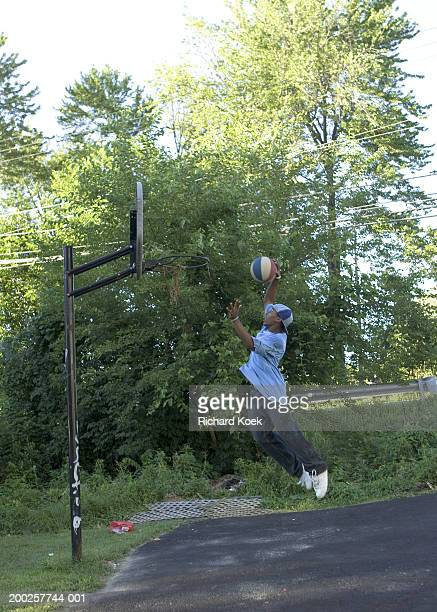 Teenage boy (13-15) playing basketball outdoors, side view