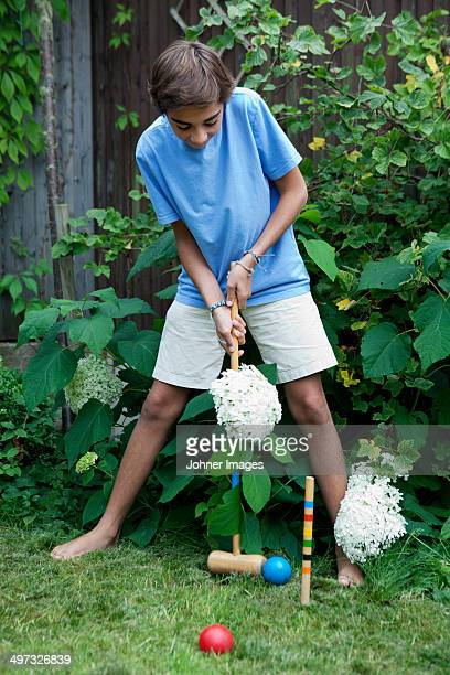 Teenage boy playing croquet, Sweden