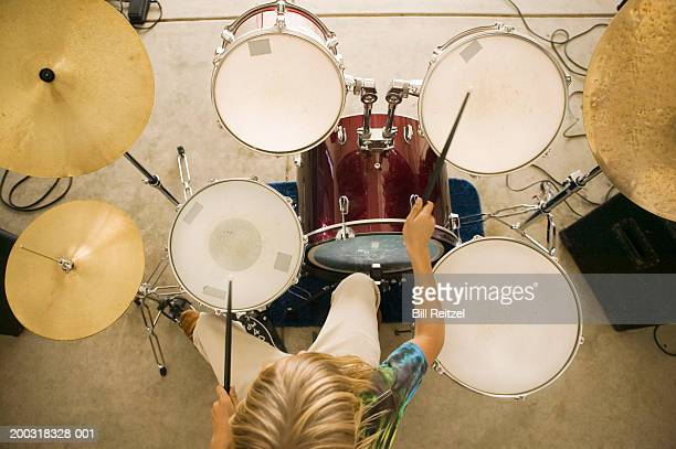 Teenage boy (13-15) playing drums, overhead view