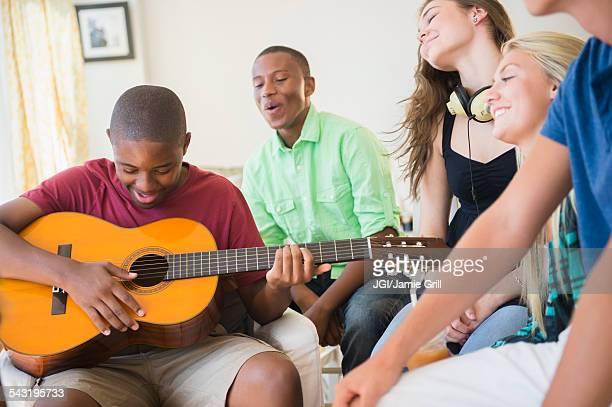 Teenage boy playing guitar at party