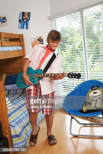 Teenage boy (16-18) playing guitar in bedroom : Stock Photo
