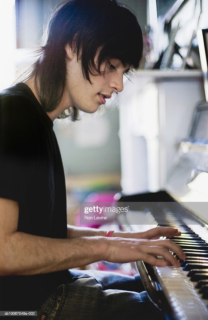 Teenage boy (14-15) playing piano, close-up : Stock Photo
