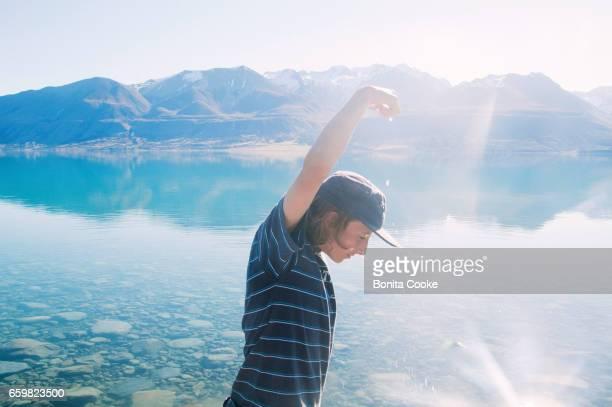 Teenage boy playing with water at Lake Pukaki, Mount Cook