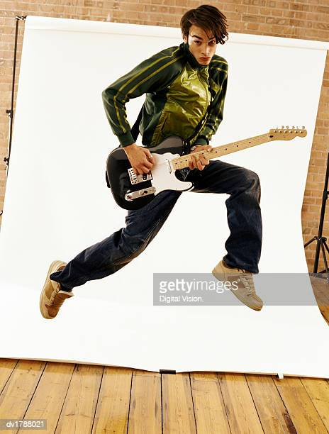 Teenage Boy Plays an Electric Guitar, Jumping Mid Air in Front of a Backdrop in a Studio