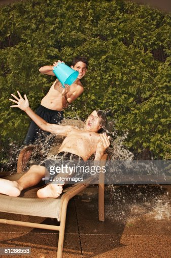 Teenage boy pouring water on friend : Stock Photo