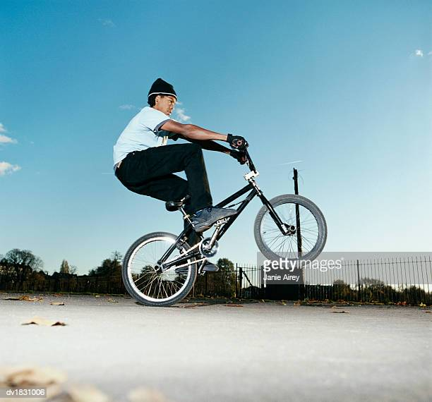Teenage Boy Practices a Stunt on His Bicycle in a Playground