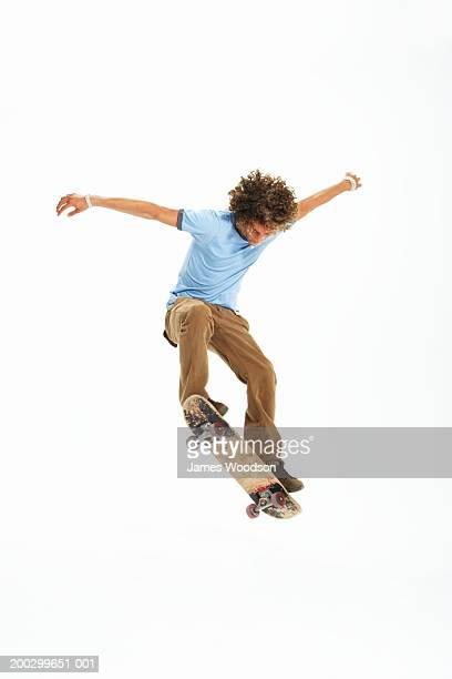 Teenage boy (16-18) practicing skateboard trick, arms outstretched
