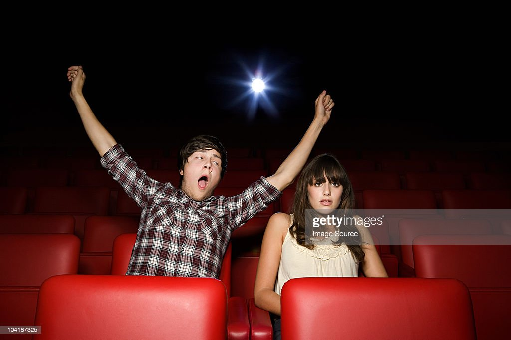 Teenage boy pretending to yawn in the movie theater : Stock Photo