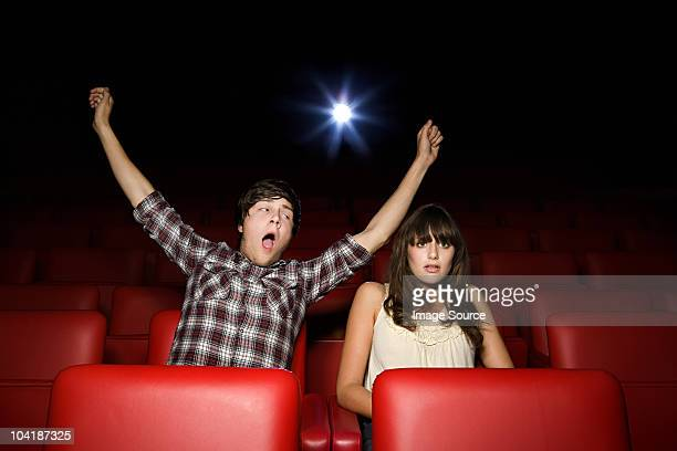 Teenage boy pretending to yawn in the movie theater