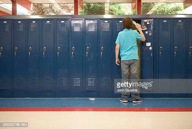 Teenage boy (13-15) putting books in locker, rear view