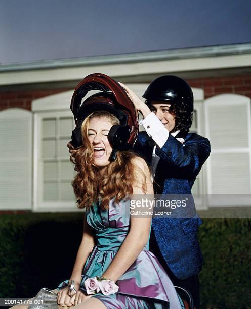 Teenage boy (14-16) putting helmet on girl