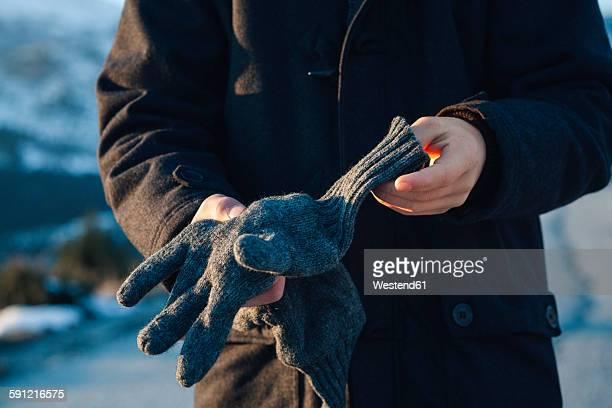 Teenage boy putting on gloves
