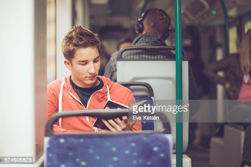Teenage boy reading a book on the tram