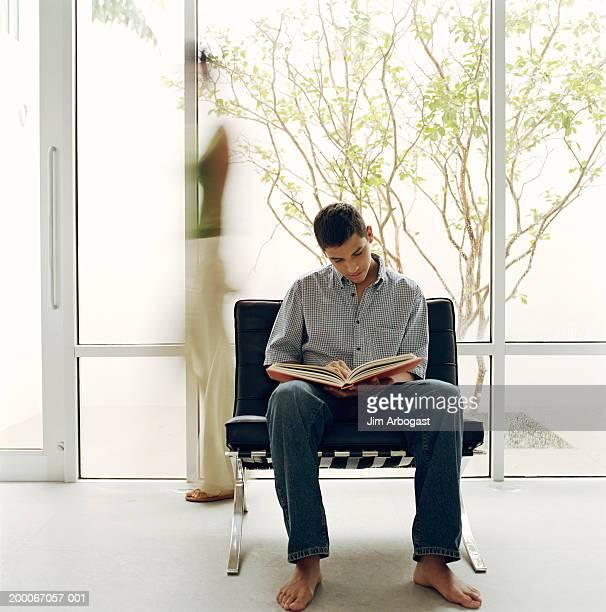 Teenage boy (14-16) reading book, mother  behind him (long exposure)