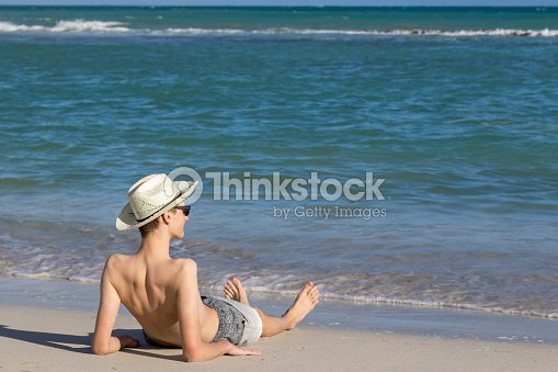 teenage boy relaxing at the sea shore on sandy beach and enjoying