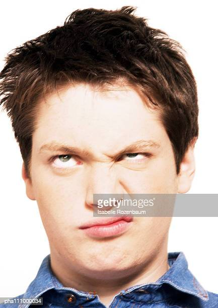 Teenage boy rolling eyes and raising one corner of mouth, head shot, close-up, white background