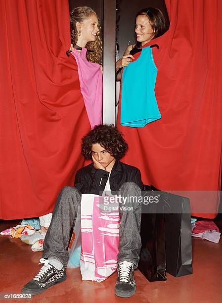Teenage Boy Sits Waiting For His Female Friends Who Compare Tops From Behind Fitting Room Curtains
